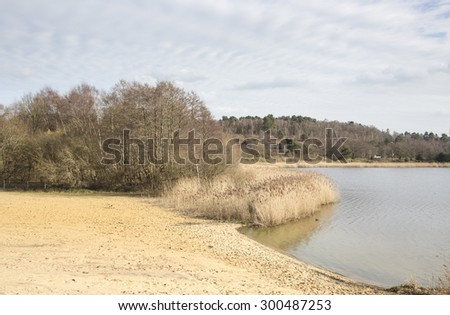 Frensham Great Pond, Frensham Common, Waverley, Surrey, UK, in winter with lake and sandy beach area under dramatic sky - stock photo