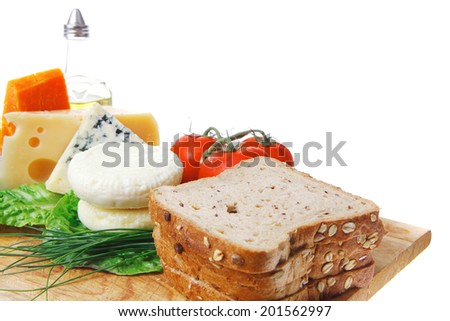 fresh aged french cheeses chops on big cutting board with tomatoes olive oil, rye bread and green chives isolated over white background - stock photo