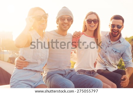 Fresh air and good friends. Four young cheerful people bonding to each other and smiling while sitting on the roof of the building together - stock photo