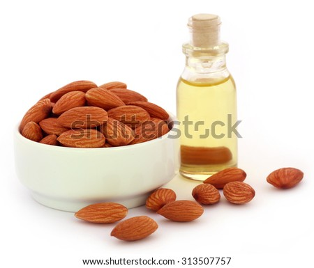 Fresh almonds with bottle of oil over white background - stock photo