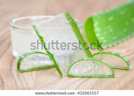 Fresh aloe leaves and a bowl of aloe gel - concept of organic skincare - stock photo