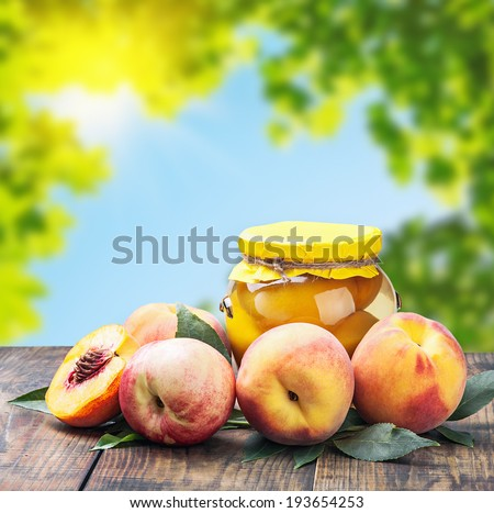 fresh and canned peaches on nature background - stock photo