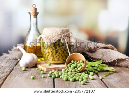 Fresh  and canned peas in bowl and glass jar on napkin, on wooden table, on bright background - stock photo