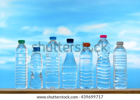 Fresh and clean drinking water in assortment of capped bottles on sky background - stock photo