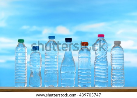 Fresh and clean drinking water in assortment of capped bottles with water droplets on sky background - stock photo