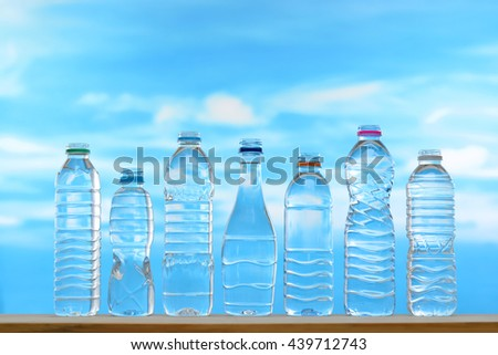 Fresh and clean drinking water in assortment of uncapped bottles  on sky background - stock photo
