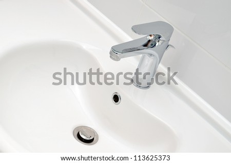 Fresh and clean washbasin and chrome tap - stock photo