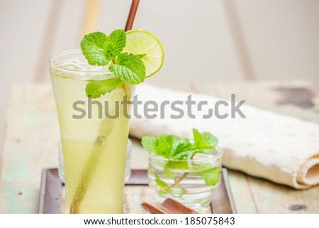 Fresh and cold ice green tea with sliced lime and mint - stock photo