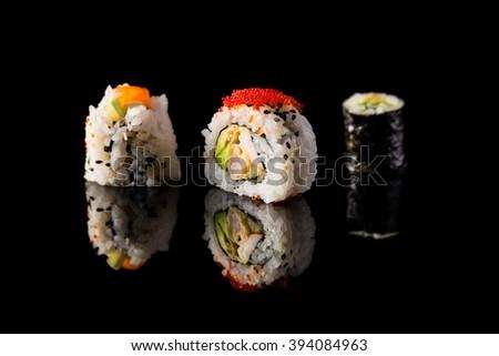 Fresh and delicious maki sushi isolated on black background. - stock photo