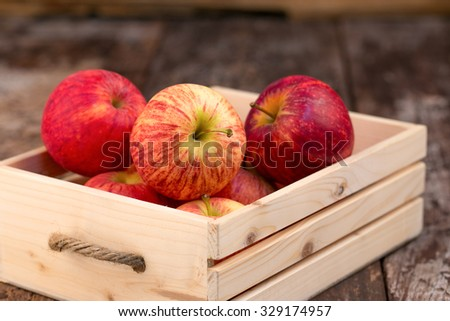 Fresh and delicious red Ambrosia apples in a wooden crate - stock photo