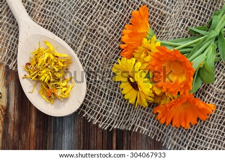 Fresh and dried calendula on sacking on old wooden background - stock photo