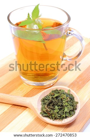 Fresh and dried nettle with cup of hot beverage, concept for healthy eating - stock photo