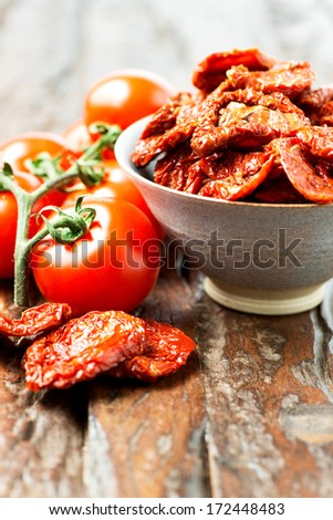 Fresh and dried tomatoes on old wooden table - stock photo