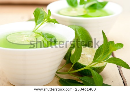 fresh and healthy mint infusion tea tisane with lime - stock photo