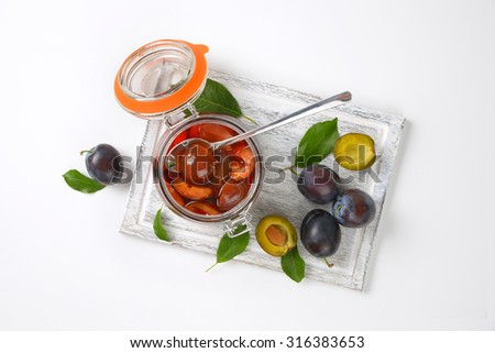 fresh and preserved plums on wooden cutting board - stock photo