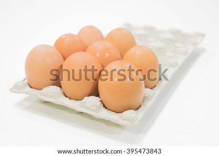 Fresh and raw chicken eggs in a tray - focus on the front egg - isolated with white background - soft glowing light - stock photo