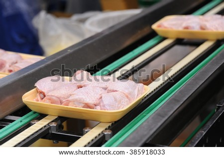 Fresh and raw chicken meat on conveyor belt in factory - stock photo