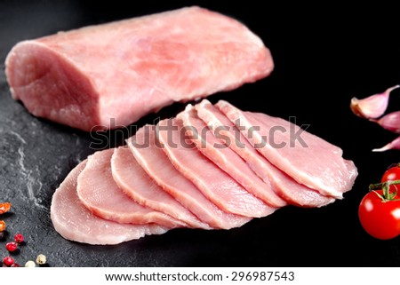 Fresh and raw meat. Pork tenderloin, loin  medallions Steaks in a row ready to cook. Background black blackboard - stock photo