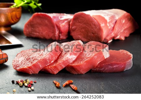 Fresh and raw meat. Sirloin medallions steaks in a row ready to cook. Background black blackboard  - stock photo