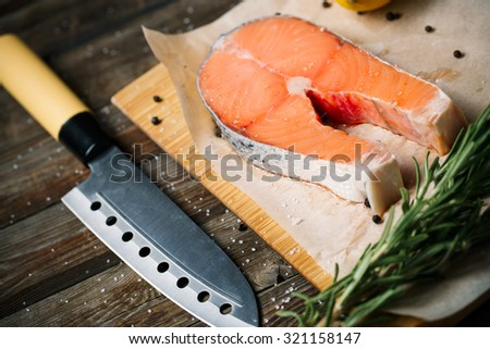 Fresh and raw steak salmon on wooden cutting board with rosemary and pepper - stock photo