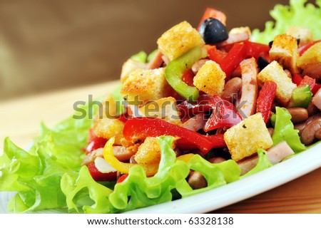 Fresh and tasty salad  on plate, wooden table - stock photo