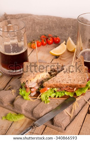 Fresh and tasty sandwich with Roast Meat, Cheese and Vegetables. Sandwich Served with Mug of Beer. - stock photo
