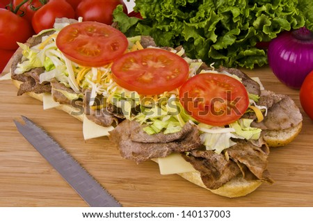 Fresh and tasty submarine sandwich on a wooden plank, vegetables in  background. - stock photo