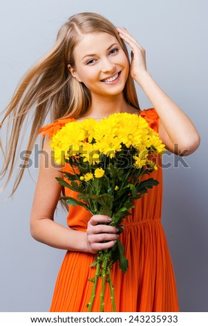 Fresh and tender. Beautiful young woman in pretty dress holding bouquet of flowers while standing against grey background   - stock photo