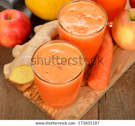 Fresh apple and carrot juice on brown background - stock photo