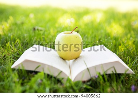 Fresh apple and open book - stock photo