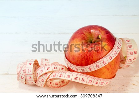 Fresh apple with measure tape on white wood background, object for diet concept.  - stock photo