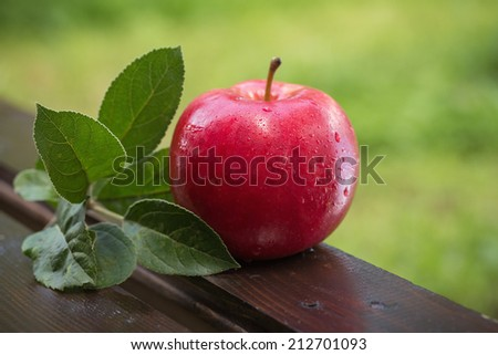 Fresh apple with water droplets, on an old wood table outdoors - stock photo