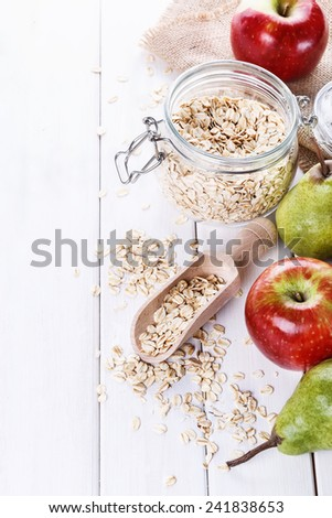 Fresh apples and pears and rolled oats over white wooden background with copyspace. Selective focus, shallow DoF - stock photo