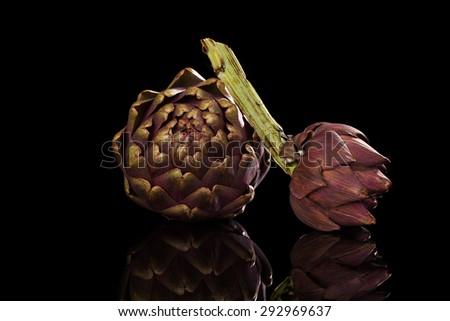 Fresh artichoke isoalted on black background. - stock photo