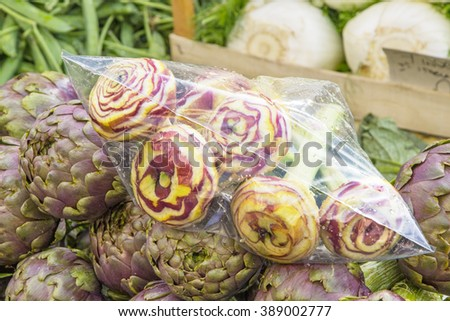 fresh artichokes wrapped in a plastic bag in an open market in Rome - stock photo