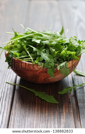 Fresh arugula leaves in wooden bowl on a wooden background - stock photo
