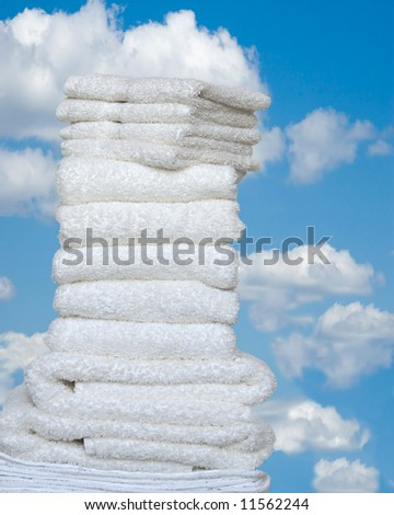 Fresh As Spring - A stack of folded white towels and wash cloths outside against a bright blue sky with white puffy clouds. - stock photo