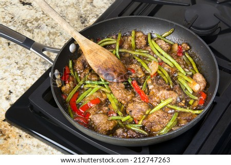 Fresh Asian style beef stir fry with green beans, peppers, onions in teriaki marinara sauce cooking in a saute pan on a stove top. - stock photo