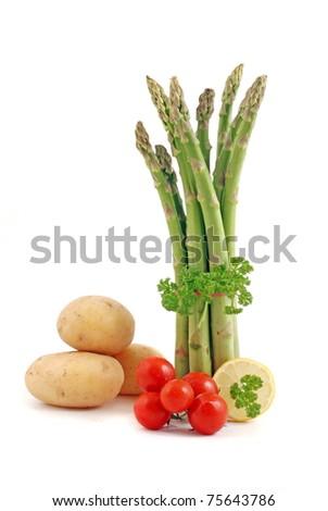 Fresh asparagus, cherry tomato and potatoes on white background - stock photo