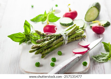 Fresh asparagus,radishes, cucumber and spring herbs on the wooden board - stock photo