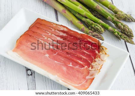 Fresh asparagus with delicious ham on plate. Preparation for cooking asparagus rolled in ham. - stock photo