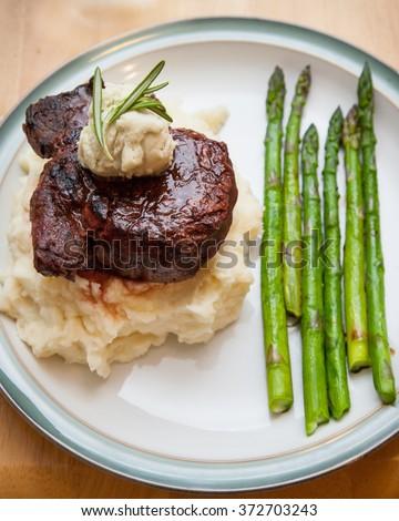 Fresh asparagus with Gorgonzola butter topped filet mignon steak - stock photo