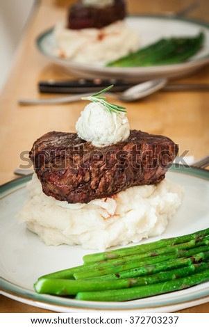 Fresh asparagus with Gorgonzola butter topped filet mignon steak side view with bokeh - stock photo