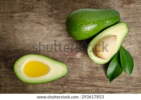 fresh avocado and  avocado like a bowl for oil on wooden background - stock photo