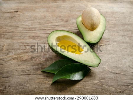 fresh avocado and half of avocado like a bowl for oil on wooden background.side view - stock photo