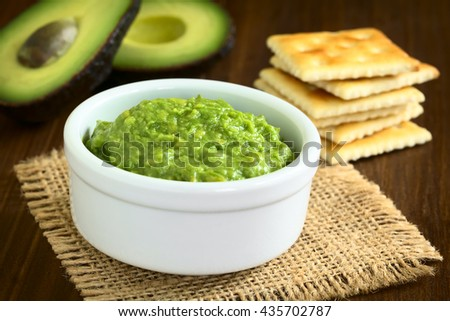Fresh avocado cream or guacamole with soda crackers and half avocados in the back, photographed with natural light (Selective Focus, Focus in the middle of the avocado cream) - stock photo