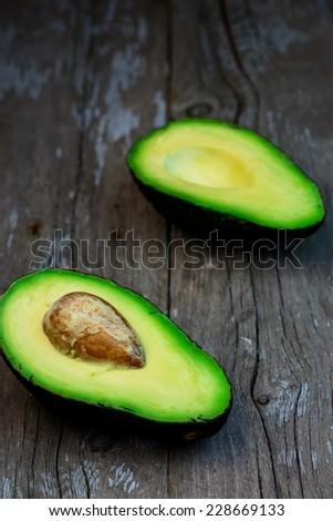 fresh avocado on wooden board, selective focus - stock photo