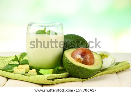 Fresh avocado smoothie on wooden background - stock photo