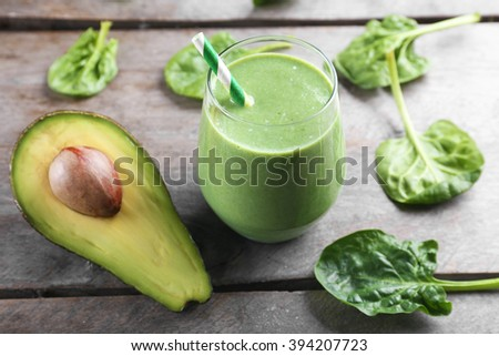 Fresh avocado smoothie on wooden background - stock photo