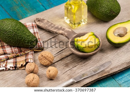 fresh avocados on wooden background. Healthy food, diet. Vegetarian. Avocado oil - stock photo
